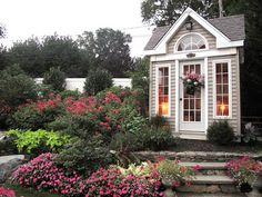 "Garden sheds don't have to look like ""garden sheds"" anymore. This garden shed boasts its beauty with gray and white contrasts, windows and doors with indoor lighting. The flowers growing around it are the perfect backdrop for this fanciful place to pot flowers, herbs, etc."