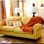 This analogous living room includes hues of red on the curtains and furniture, orange in the pillows, yellow - oranges on the curtains, and yellow on the couches.