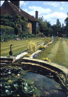 """Deanery Gardens, """"The house & garden seen from the pergola above the circular pool at the north-west end of the narrow canal."""" 1"""