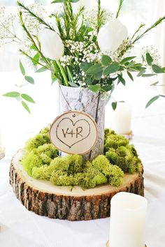 Engraved wood rounds and moss combine to create a simple but elegant wedding centerpiece with a personal touch.