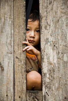 A child is glancing through a gap in the wall of a daycare at the refugee camp Mae Ra Ma Luang in Thailand. Largely from Myanmar's ethnic minority Karen and Karenni groups, 140,000 Burmese refugees are sheltering in nine camps in isolated patches of jungle along the frontier to Myanmar. Over half a million displaced Burmese fleeing aggressive military operations in Myanmar are creating a humanitarian disaster area along its border with Thailand. Aid agencies maintain that Burmese troops…