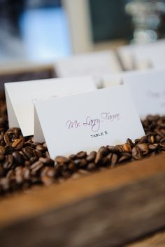 Wedding attendees found their purple-and-white escort cards displayed in a wooden box filled with coffee beans. #escortcards Photography: Sarah & Ben. Read More: http://www.insideweddings.com/weddings/florida-wedding-celebration-with-vibrant-colors-and-wooden-details/644/
