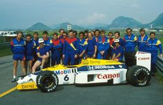 Williams team group shot, featuring team members, the drivers Nigel Mansell (left) and Nelson Piquet (right) and Piquet's Honda-powered FW11
