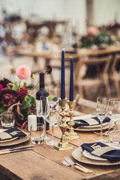 wedding styling navy blue candles gold ornate sticks with navy blue napkins name places flowers tables natural wood rustic wedding vibe #beachweddingcandles
