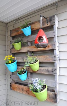 Hang flowerpots from a pallet to create a vivacious vertical garden.