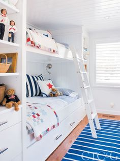 A snug bunkroom sleeps three thanks to the pull-out trundle bed; the blue-and-white striped rug is from Pottery Barn Kids.