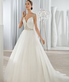 This dreamy Tulle ball gown with plunging V-neckline is embellished with crystal jeweling on the waist.  The sheer beaded cap sleeves transition into a magnificent jewel embellished low sheer back with button closure.  The back features a Chapel length train.