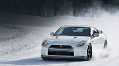 2016 Nissan GT-R sports car black edition driving in snow shown in pearl white