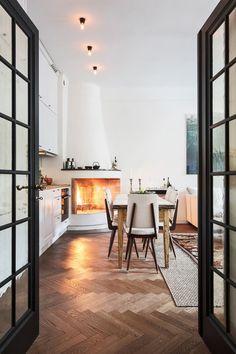 Herringbone wood floor, steel framed French doors, corner fireplace - monochromatic and earthy