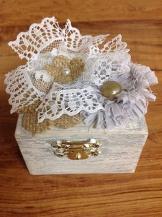 This is a beautiful vintage style wood ring box. The box is distressed in gray and white. The top of the box is decorated with handmade white lace, gray, and burlap flowers. The box measures It is the perfect unique touch for your ring bearer. Grey And White, White Lace, Gray, Wooden Ring Box, Ring Bearer Box, Burlap Flowers, Wood Rings, Grey Wood, Diy Wedding Decorations