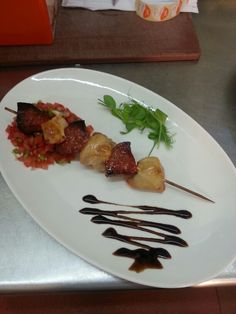 Chicken and chorizo skewer laid on salsa mix with balsamic glaze