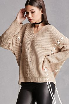 An oversized waffle knit sweater featuring contrast lace-up panels throughout, hanging self-ties at the hem, a V-neckline, cable knit panel on the front, dropped shoulders, long sleeves, and a billowy silhouette. This is an independent brand and not a Forever 21 branded item.