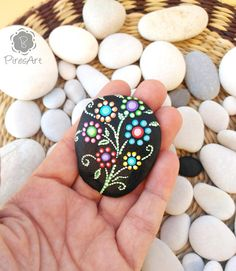 Floral style hand painted beach stone. This is a stone which is painted with acrylic paint with brush. The motive are flowers by little dots in differents colors. The background is painted in black color. This type of rocks allows you to decorate small table centers and the favorite corners of your home. Ideal gift to new house or for those who like to collect hand painted rocks. Perfect for people who like those little details that make your home different and unique. Size and weight: we...
