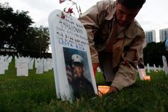"""""""Carlos Arredondo places a candle next to a cardboard tombstone with a photograph of his son Marine Lance Corporal Alexander Arredondo who was killed in Najaf, Iraq.The tombstones were setup in silent protest to the rising toll of U.S. military deaths in Iraq."""" (Photo by Joe Raedle/Getty Images) - Carlos is also the """"hero in the cowboy hat"""" seen in many of the Boston Marathon images."""