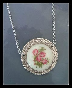 Pretty round cream and rose print cabochon in a pale gold nearly silver round decorative frame dangling from 18'' necklace chain. Such a pretty necklace made using recycled jewellery parts and has a nice vintage feel to it. We ship worldwide. We post to the UK and Ireland for FREE.