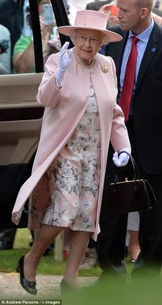 The Queen, dressed in a pink floral dress with matching coat and hat, makes her way into t...
