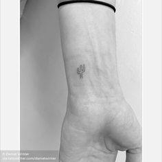 Miniature cactus tattoo on the wrist.