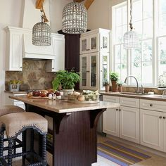 Eye-catching light fixtures add style to this neutral kitchen. More kitchen design ideas: http://www.bhg.com/kitchen/color-schemes/neutrals/reasons-to-love-white-kitchens
