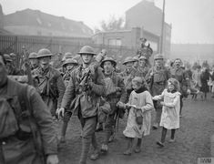 Troops of the 8th Battalion, Liverpool Regiment (57th British Division, XI Corps), swarmed by local children, entering Lille, 18 October 1918. The soldier carrying a Lewis machine gun is Private Arthur John O'Hare.