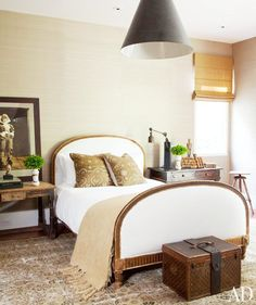 A bedroom in the home of Ellen Degeneres boasts a Louis Vuitton trunk at the end of an arch upholstered bed