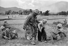 U.S. air cavalryman helps an old Vietnamese woman up a hill, January 5, 1968. She had grown tired as she and her neighbours had to flee their village to a refugee camp. Other villagers had refused to assist her because, according to Vietnamese custom, they would then have borne responsibility for her for the remainder of her life.