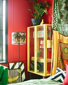 Bright colored furniture and red walls help make this stylist's dream bedroom.
