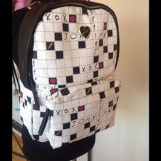 """Betsey Johnson KITCHI CROSSWORD Backpack Betsey Johnson KITCHI CROSSWORD Backpack BR21825!   add tee shirt size medium for 15.00 additional  Fashion speaks louder than words! Say what's really on your mind with Betsey Johnson's fun crossword backpack, featuring an ultra-spacious, rose-printed interior.  For the puzzle lovers """"Smart is the new sexy!""""       Shiny PVC backpack Zipper closures Crossword exterior design! Gold-tone hardware Exterior signature logo plate Measurements: Approximately…"""