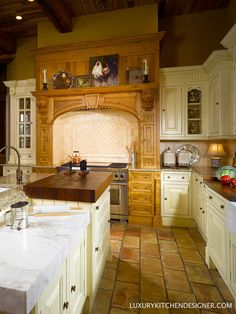 A thick, iroko chopping block is situated between the sink and the range.  Cabinetry by Clive Christian in Antique French Oak and Antique Cream.