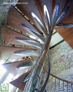 Escalera caracol de acero cromado y madera.