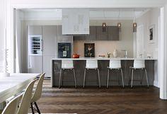 De tre lamporna ovanför köksön är från Kartell. Fläktkåpan är specialbyggd och dekorerad med kakel. Kök från Siematic med köksö i corian. Foto: Martin Löf