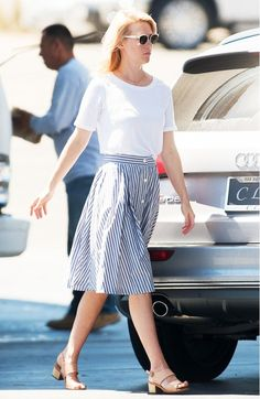 January Jones wears a white t-shirt tucked into a striped knee-length skirt, white sunglasses, and neutral sandals