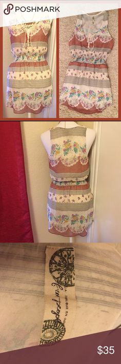 "Free People Floral Scoop Neck Sundress *EUC* This lovely boho summery dress is breezy and features pockets and lining. Has a tie in the front and features a pattern of flowers and stripes. The elastic cinched waist ensures a flattering and comfortable fit. The base is off white/cream with orange, yellow, green, black and purple designs. Gently used, I haven't found any signs of significant damage or wear. Length: 34"", Waist: 24"", Bust: 30"" Free People Dresses"
