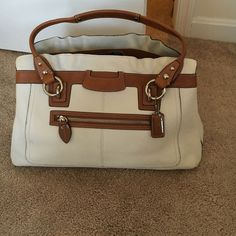 Coach bag white and tan Coach purse. White and tan in color. Very classy. It is in great shape. It has a few mark on the outside (on the front and on the bottom). I zoomed into one of the marks on the front - see pictures. Inside is in fabulous condition. Also comes with the protective bag for storage. Coach Bags Satchels