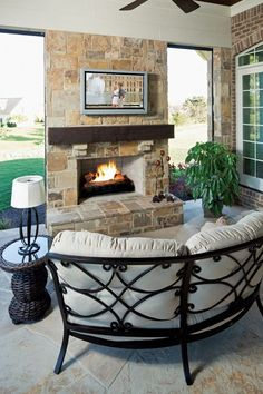 Indianapolis Monthly's 2012 Dream Home: An exclusive look inside the city's premier show home. A crisp color palette of mostly white-and-cream walls and furniture—with splashes of color throughout—complements the builder's architectural design. #outdoor #fireplace #seatingarea