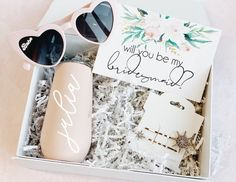"""take the stress out of shopping for your bridesmaids with our cute AF curated  bridesmaid proposal boxes they will ALL love way past the big day!!Treat your gals to something nice!curated + styled by thesimplebridecoBOX CONTENTS:(1) White Box filled with white krinkle paper(1) Customizable Stainless Steel champagne flute(1) pair of babe heart sunglasses (1) set of our celestial hair pins(1) Floral """"will you be my bridesmaid"""" card ( title customizable)Please note that these boxes ship out in the Bridesmaid Gift Boxes, Bridesmaid Proposal Gifts, Be My Bridesmaid Cards, Bridesmaid Baskets, Gifts For Wedding Party, Bridal Gifts, Wedding Ideas, Bridal Parties, Diy Wedding"""
