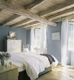 Love the grey blue walls with the white curtains and the exposed pale beams. Just imagine the view from those windows...