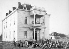 Chemawa Indian School small boys dorm, Salem, Oregon. 1901. A large group of small boys sit on the grass in front of a three story building at the Chemawa Indian School. Beside them stands a woman holding a bicycle. Another school building can be seen on the right. Collection: Estelle Reel Repository: Eastern Washington State Historical Society
