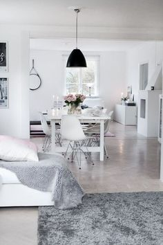 light floors, white walls, plush rug and throw, black accents, white furniture