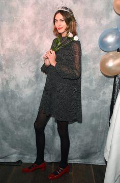 Alexa Chung in a black printed mini dress, tights and red flats