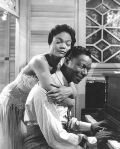 """Eartha Kitt hugs Nat King Cole, playing the piano in the role of W.C Hardy, in scene from the 1958 movies """"Saint Louis Blues"""""""