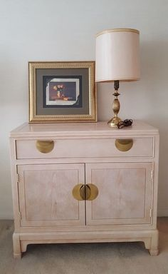 """Lineage blond wood storage cabinet with table lamp and wall art. Buffet cabinet 35.5""""Wx17""""Dx32.5""""H with single drawer and cabinet storage below. Brass table lamp with silk shade. Framed & matted wall art, behind glass 20.5""""Wx19""""H. All pcs very good cond."""