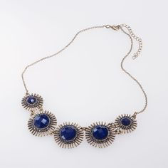 This statement necklace has 5 midnight blue faceted beads set in antique gold finished settings that are surrounded by circular rows of spikes. Don't forget to check out the matching earring.