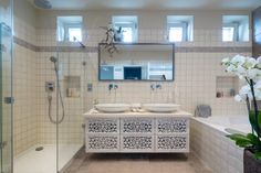 White elegant master bathroom features walk in shower, white handmade antique cupboard designed by Monika White.