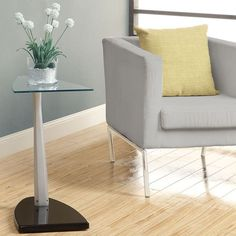 Redecorate your favorite space with this modern accent table, featuring a glossy black base. This piece also offers a flipper-shaped top that is constructed out of tempered glass.