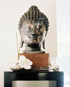 Details Make The Design. Buddha statue and wooden side table. Interior Designer: Vicente Wolf.