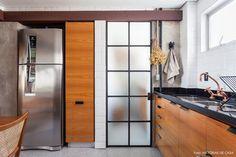 Cozinha integrada tem piso em formato de colméia, subway tiles, metais na cor cobre e porta de serralheria.