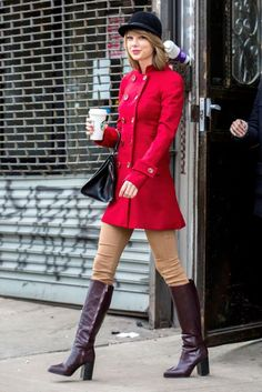 Modernized Equestrian Taylor pairs her bright red riding coat with skinny tan pants, knee high boots and a helmet-like hat. On her way to the stables? Nope — just Whole Foods!