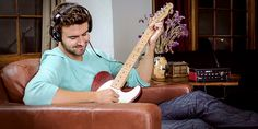 guitarist jamming on Line 6 AMPLIFi TT desktop amp modeler wearing headphones