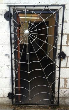 A metal door fashioned to look like a spiderweb. Welcome to my garden, said the spider to the fly...