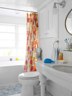 "When designer Tara Seawright's clients bought an outdated waterside cottage, they turned to her for help modernizing the space, on a tight budget. ""By painting the floors a bright white and using strategic pops of color — like a colorful shower curtain — against a neutral background we gave the home a more current look,"" says the designer."
